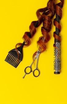 Parrucchiere stilista strumenti, forbici, pettine, spazzola, su uno sfondo giallo, verticale,