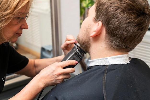 Parrucchiere che si prende cura della barba di un cliente
