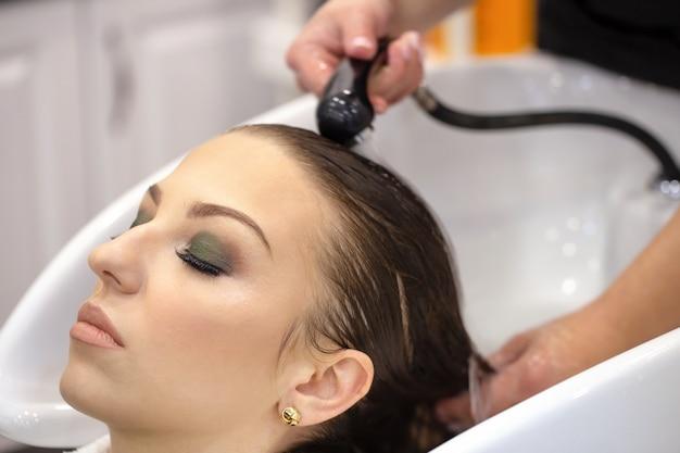 Il parrucchiere lava i capelli di una giovane ragazza