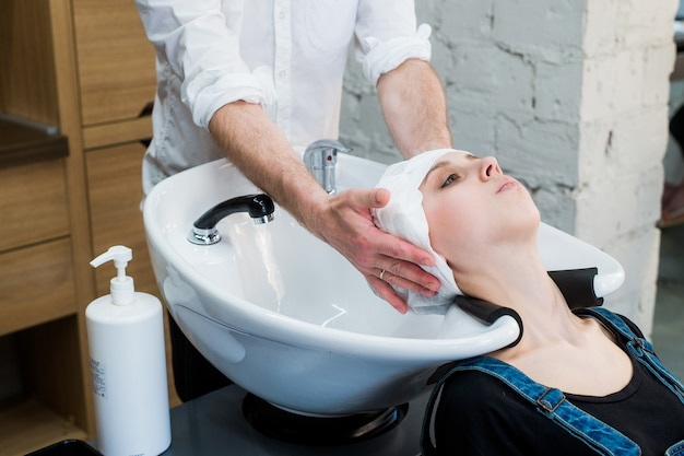 Parrucchiere che lava i capelli al cliente prima di fare l'acconciatura