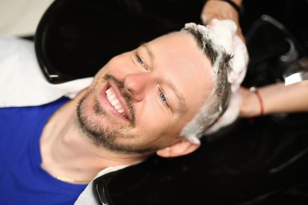 Parrucchiere che lava la testa di un giovane uomo nel lavandino