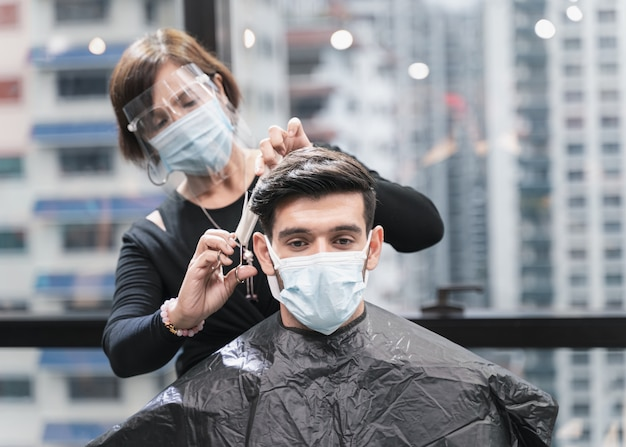 Parrucchiere con misure di sicurezza per covid-19 o coronavirus, capelli tagliati un uomo in una maschera di medicina