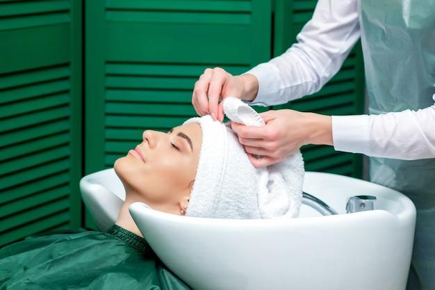 Parrucchiere avvolgere i capelli della donna in un asciugamano dopo aver lavato la testa nel salone di bellezza, primi piani.