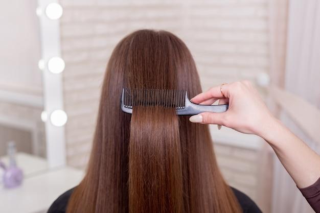 Parrucchieri spazzolatura a mano lunghi capelli castani nel salone di bellezza