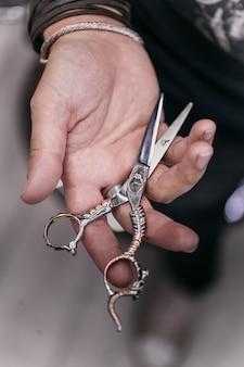 Forbici da parrucchiere barbiere. un uomo con i tatuaggi tiene in mano delle forbici vintage. l'uomo dal barbiere.