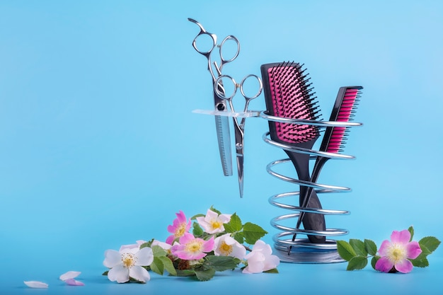 Strumenti per parrucchieri su supporto in metallo decorato con delicati fiori rosa