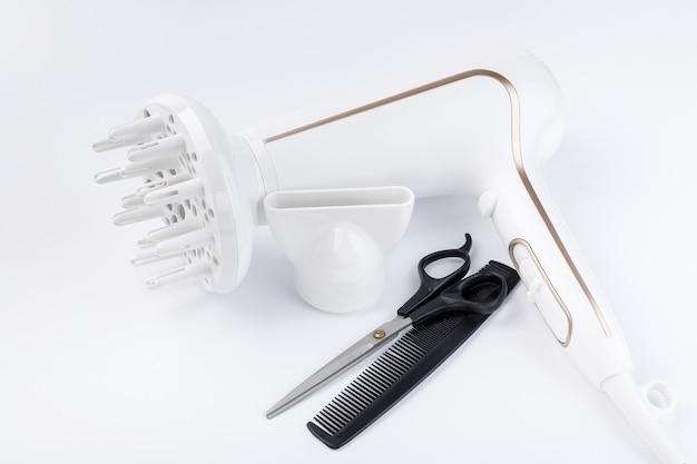 Asciugacapelli con diversi allegati forbici e pettine su uno sfondo bianco
