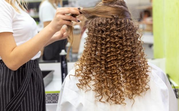 Vista posteriore di acconciatura. parrucchiere che fa acconciatura alla donna rossa dei capelli biondi con capelli lunghi nel salone di bellezza