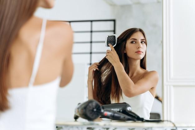 Acconciatura e cura quotidiana dei capelli a casa. allegra signora caucasica millenaria che pettina lunghi e belli capelli lisci nell'interno del bagno al mattino