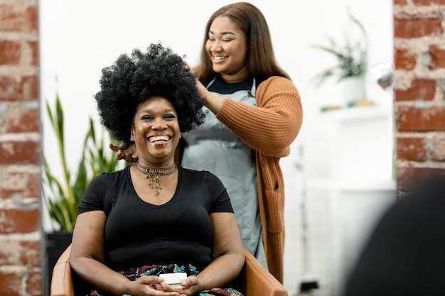Parrucchiere che taglia i capelli a una cliente in un salone di bellezza