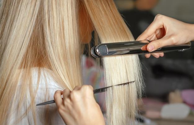Le mani dell'hairstylist raddrizzano i capelli con la piastra per capelli