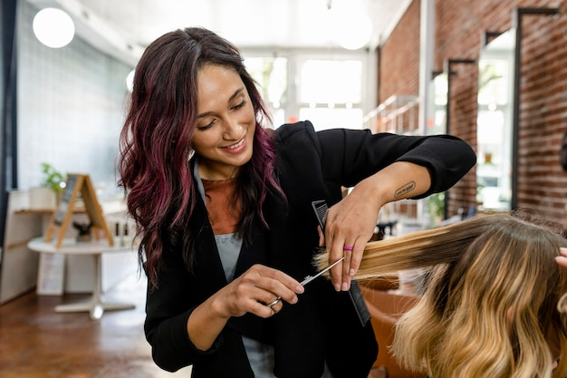Parrucchiere che taglia i capelli della cliente in un salone di bellezza