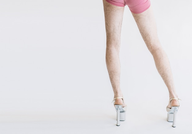 Gambe pelose in tacchi alti in mutandine rosa isolate su bianco
