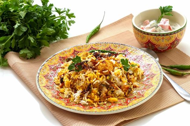 Biryani di pollo indiano halal servito con raita di pomodoro allo yogurt