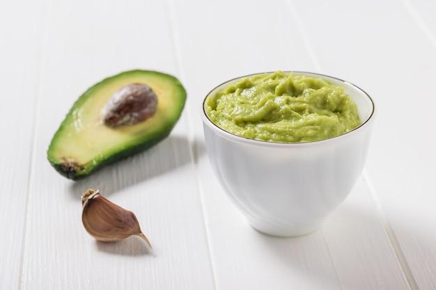 Mezzo avocado, aglio e una ciotola di guacamole su un tavolo di legno bianco. dieta vegetariana cibo messicano avocado. cibo crudo.