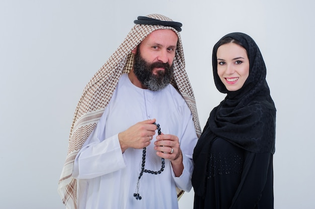 Metà corpo di coppia araba in posa insieme isolato su sfondo grigio.
