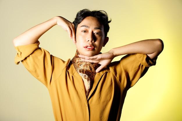 Ritratto a metà corpo di 20s asiatici lgbtqia + gay uomo capelli neri indossano camicia gialla con sciarpa. il maschio fa moda pone metà corpo su sfondo beige