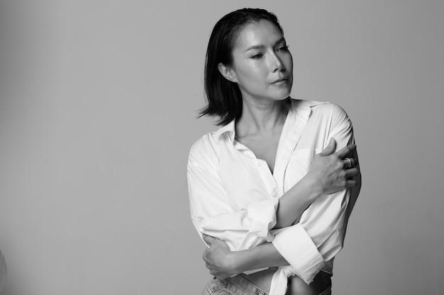 Mezzo busto ritratto di 40s asian lgbtqia + donna capelli neri bianchi vasti pantaloni di jeans corti. transgender 30s donna express sentirsi felice sorriso molte pose su sfondo bianco isolato