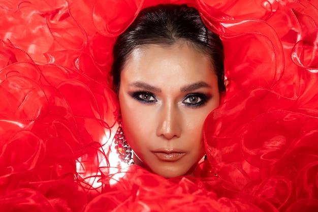 Ritratto di metà corpo di donna transgender asiatica in abito da sera rosso fantasia cabaret carnevale su sfondo scuro