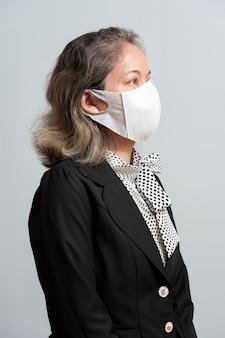 Ritratto a metà corpo di donna di razza mista di mezza età in abbigliamento formale che indossa una maschera chirurgica bianca