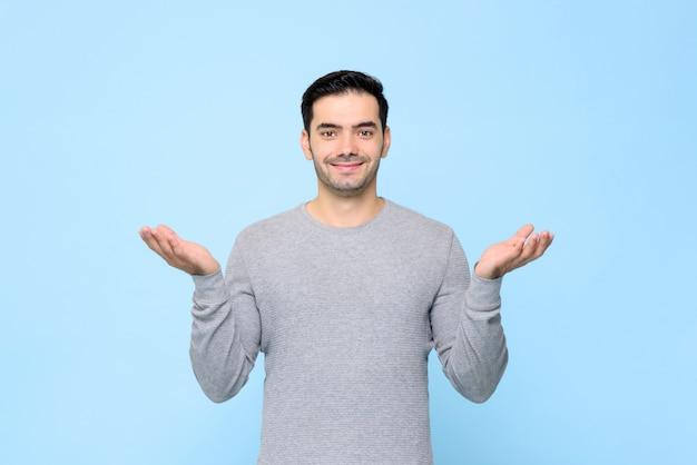 Ritratto mezzo del corpo dell'uomo sorridente in maglietta grigia con il gesto di mano aperto in blu-chiaro