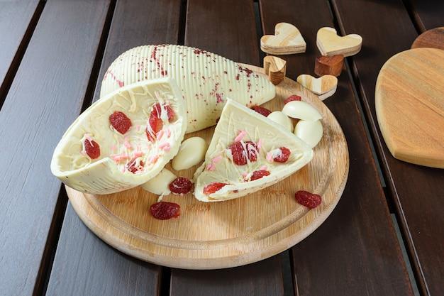 Mezzo uovo di pasqua rotto cioccolato bianco con fragole candite su un piatto di legno accanto ai cuori