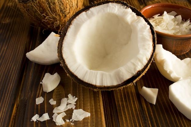 Mezza noce di cocco e patatine fritte sulla superficie di legno marrone