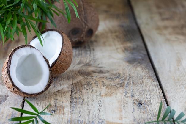 Mezza noce di cocco e un ramo di palma si trovano su un tavolo di legno. copia spazio