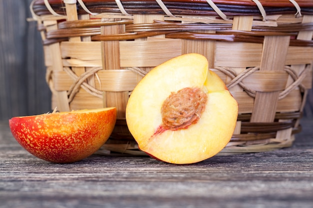 Una pesca tagliata a metà sdraiata su un tavolo con un cesto di vimini per la frutta