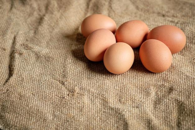 Mezza dozzina di uova marroni su tela di sacco marrone