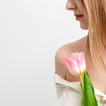 Ritratto mezzo volto di una giovane e bella donna caucasica con un tulipano rosa su sfondo bianco