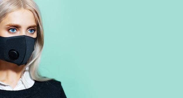 Ritratto in studio a metà viso di giovane ragazza con occhi azzurri e capelli biondi, che indossa una maschera respiratoria nera contro il coronavirus, sfondo di ciano, colore acqua menta con spazio di copia.
