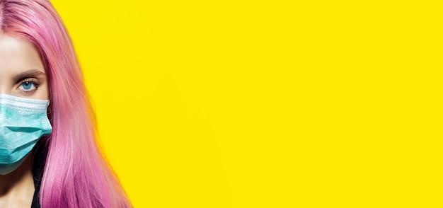 Metà volto femminile, giovane ragazza con i capelli rosa e gli occhi azzurri, che indossa una maschera antinfluenzale su giallo