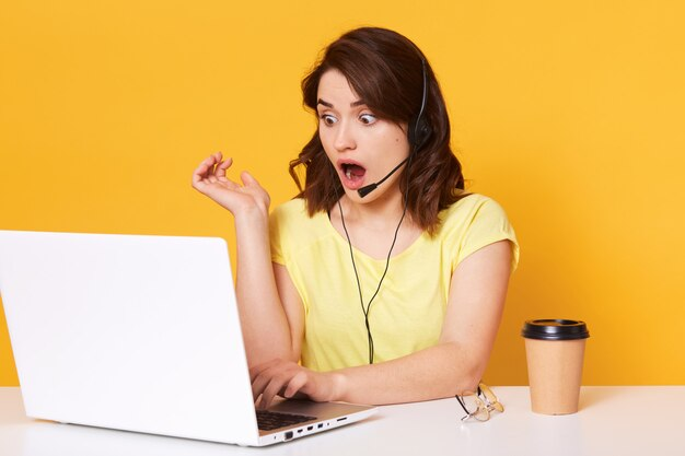 Foto a mezzo busto dell'operatore della donna che si siede con la bocca aperta, esaminando computer portatile sullo schermo, isolato sopra giallo