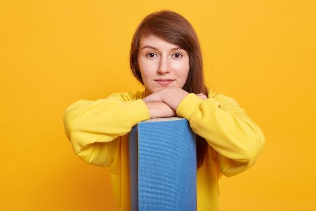 Mezzo busto di giovane femmina in posa con materassino blu