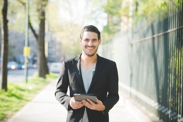 Mezza lunghezza del giovane ragazzo italiano bello camminare attraverso la città utilizzando un tablet