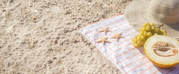 Mezzo melone, uva, stelle marine sulla spiaggia. vista dall'alto, piatto. bandiera.