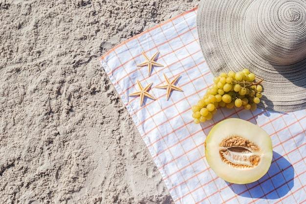 Mezzo melone, uva, stelle marine sulla spiaggia. vista dall'alto, piatto.