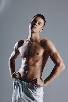 Atleta seminudo in pantaloncini bianchi che tengono le mani sulla cintura su uno sfondo grigio.