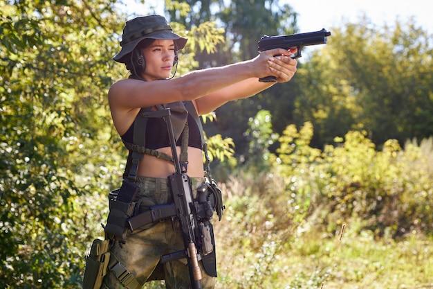 Una bella donna seminuda, mimetizzata tra le braccia durante una guerra, mira a un bersaglio