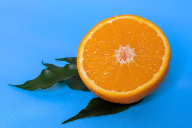 Mezza arancia tagliata a metà e affettata in foglie verdi isolate su sfondo blu, vista dall'alto, copia spazio.