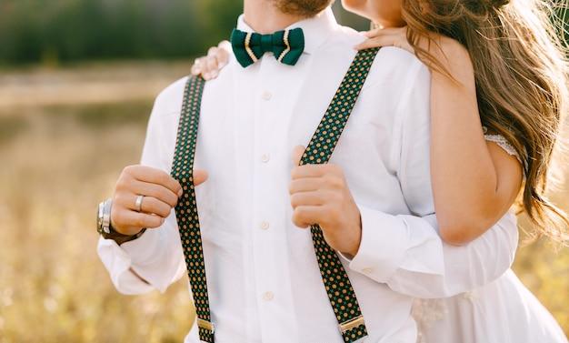 Metà ritratto della sposa che abbraccia lo sposo da dietro la sposa in uno sposo bellissimo abito bianco in bianco