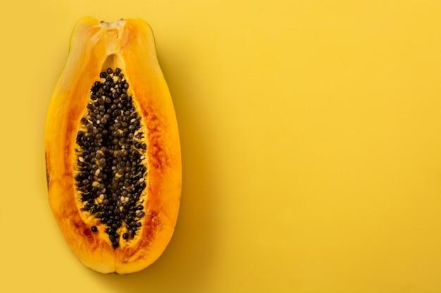 Frutta mezza matura della papaia sulla superficie gialla