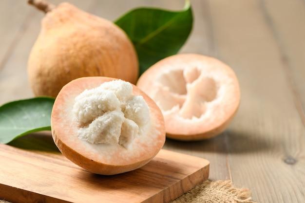 Mezzo santol su fondo di legno, santol ha un sapore aspro e la parte centrale del santol è più dolce. è un frutto molto famoso della provincia di lopburi. tailandia