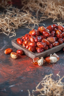 Mezzo colpo di frutti freschi di silverberry crudi all'interno e all'esterno di un vassoio di legno su uno sfondo di colori misti