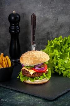 Mezzo colpo di coltello in un delizioso panino con carne e pepe verde fritto su vassoio nero su superficie grigia gray