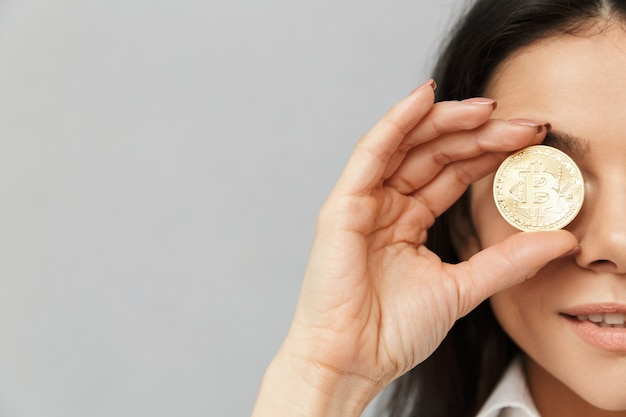 Foto a metà lato di una donna ricca con lunghi capelli castani che copre gli occhi con bitcoin dorato, isolata sopra il muro grigio