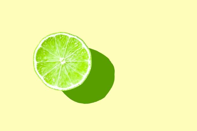 Lime fresco verde a metà affettato con ombra dura su sfondo giallo layout isolato