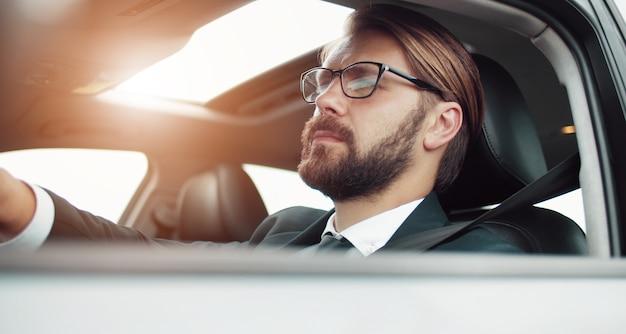 Ritratto a mezzo giro dell'uomo d'affari alla guida di un'auto con la finestra aperta, colpo dal basso