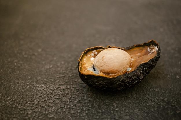 Metà dell'avocado viziato marcio malsano su sfondo scuro. avocado cattivo tagliato a metà. avocado ammuffito. copia spazio.